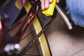 Theme repair bikes. Close-up of a Caucasian man's hand use a Chain Lubricant in a yellow lubricator for llubricator a bicycle chain on a red bicycle. poster