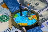 Two businessman figurines on time and money background. Worldwide business concept. International business agreement. Global corporation strategic partnership. Global business profit. Global market poster