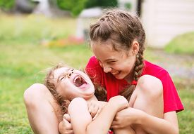 Two Happy little girls embracing and laughing at the park