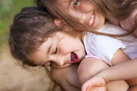 Two Happy little girls laughing and hugging at the  summer park