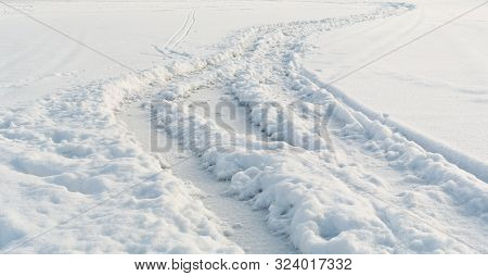 Car Tire Tracks On White Winter Snow Field Close-up Perspective View