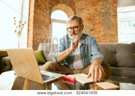 Senior Man Working With Laptop At Home - Concept Of Home Studying. Caucasian Male Model Sitting On S