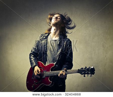 Young man playing the guitar and headbanging