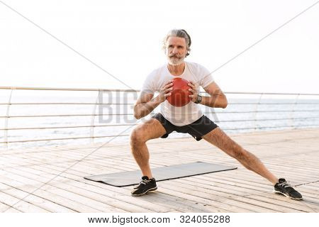 Image of gray-haired old man in sportswear using earpods while doing exercise with medicine ball near seaside in morning