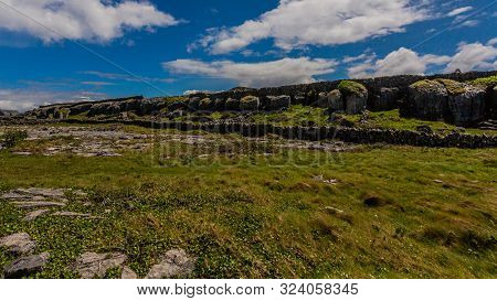 Amazing View Of Limestone Rocks Cracked By Erosion With Grykes, Stone Fences And Green Grass On The