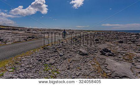 Female Cyclist On A Rural Road Between Limestone Rocks On The Coast Of Inis Oirr Island, Wonderful S