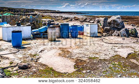Industrial Garbage Such As Plastic Barrels, Rusty Fridges And Pallet Polluting The Beautiful Rocky C