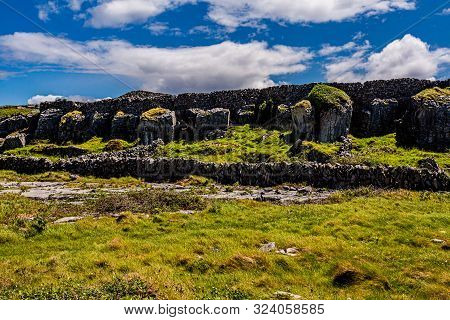 Stunning View Of Cracked Limestone Rocks That Form Grykes By Erosion Between Stone Fences And Green