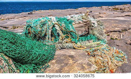 Accumulation Of Marine Litter, Such As Fishing Nets, Ropes, Wood With The Sea In The Background On T
