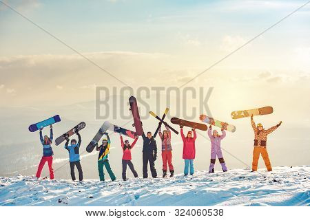 Big Group Of Happy Friends Skiers And Snowboarders Having Fun And Holding Ski And Snowboards On Moun