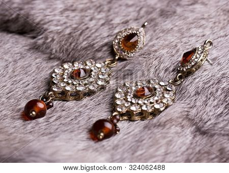 Earrings Made Of Precious Stones Lying On Gray Fur. Earrings With Stones Top View. Beautiful Female