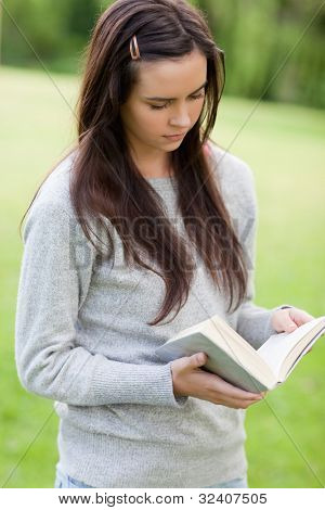 Serious young girl reading a book while standing upright in the countryside