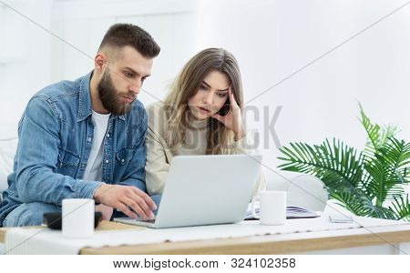 Family Budget. Young Couple Using Laptop For Managing Expanses And Making Notes, Free Space