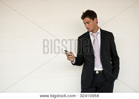 Businessman looking at his mobile phone, maybe sending SMS