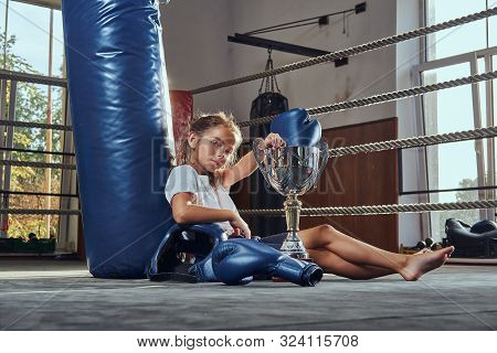 Small Pretty Girl Champion Winner In Boxing Match Is Resting On The Ring With Her Prizes.