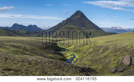Panoramic volcanic landscape of green Storasula mountain with lush moss and blue creek water between Emstrur and Alftavatn camping sites on Laugavegur trek in area of Fjallabak Nature Reserve, Iceland poster