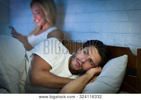 Jealousy And Cheating. Girlfriend Texting On Mobile Phone Lying With Boyfriend In Bed At Night. Low