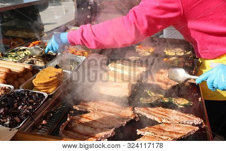 Cook With Blue Latex Glove For Hygiene While Cooking Sausages In A Street Food Stall