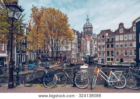 AMSTERDAM, NETHERLANDS - MAY 7, 2017: Bicycles in Amsterdam street near canal with old houses. Red lights district, Amsterdam, Netherlands
