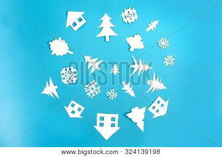 White Paper Figures Of Houses, Christmas Trees And Snowflakes On Blue Background