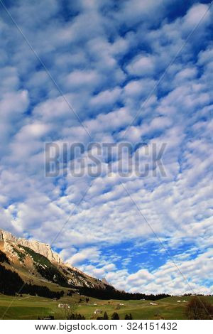 Dramatic Sky Whit Fleecy Clouds Over Houses, Farms, Meadows, Forests, Mountain Chains And The Gulmen