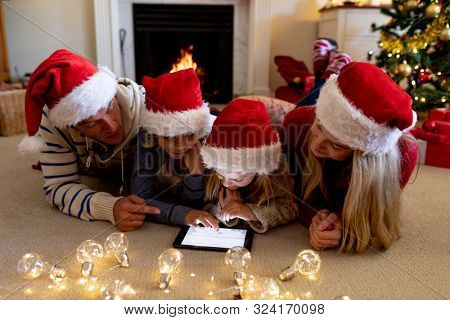 Front view of a Caucasian couple lying on the floor with their young son and daughter in their sitting room at Christmas time, wearing Santa hats and using a tablet