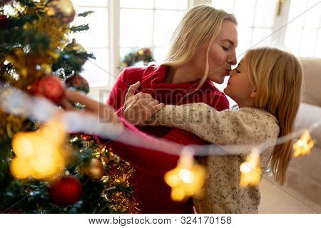 Front view of a young Caucasian woman kissing her young daughter beside the Christmas tree in their sitting room, with Christmas star decorations hanging in the foreground