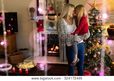 Front view of a young Caucasian woman holding her young daughter and touching noses beside the Christmas tree in their sitting room at Christmas time, with Christmas star decorations hanging in the
