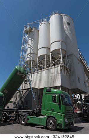 Frankfurt Am Main, Germany June 27, 2018: Cement Factory With Silos And Green Truck Mixing Silo Cons