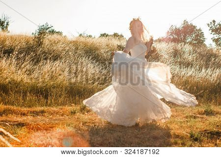 Bride On A Summer Field In White Wedding Dress Rolling And Dancing In Sunset Light. Sun Beams Seen T