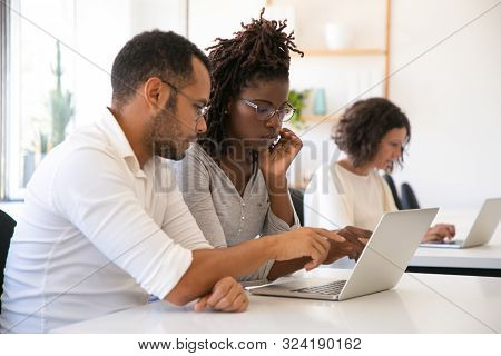 Instructor Explaining Corporate Software Specific To Intern. Man And Woman In Casual Sitting At Desk