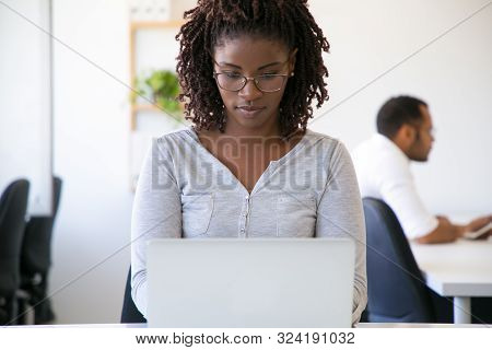 Focused Pensive African American Worker Using Laptop. Young Woman In Casual And Eyeglasses Sitting A