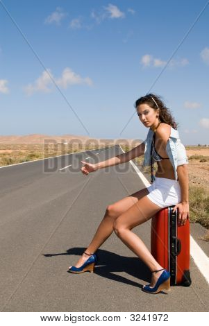 Woman In The Road Auto-Stop Sitting In Her Suitcase