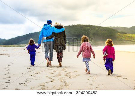 Happy Young Family Is Walking On Sandy Beach And Ocean. happy Family - Father, Mother, Baby Girls Ho
