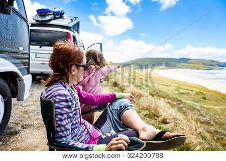 Motorhome Rv Or Campervan Is Parked On A Beach. Family On Vacation Is Sitting Outsides On Camping Ch