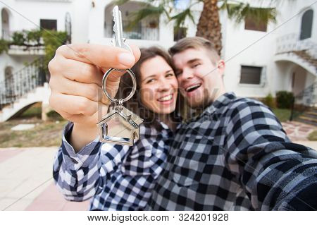Property, Real Estate And Apartment Concept - Happy Funny Young Couple Showing A Keys Of Their New H