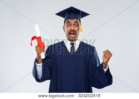 education, graduation and people concept - happy smiling indian male graduate student in mortar board and bachelor gown with diploma celebrating success over grey background