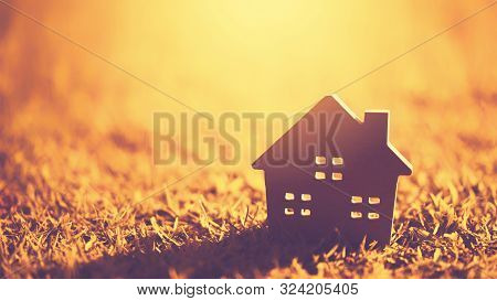 Copy Space Of Home And Life Concept. Small Model Home On Green Grass With Sunlight Abstract Backgrou