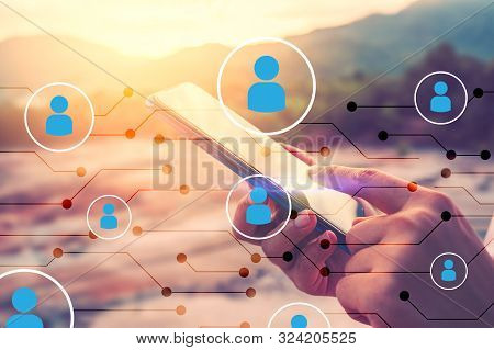 Man Hand Using Smart Phone On Top Of Mountain With People Icon And Line Dot Abstract Background. Cop