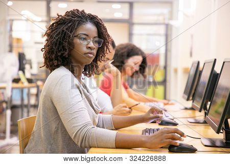 African American Adult Student Working In Computer Class. Line Of Man And Women In Casual Sitting At
