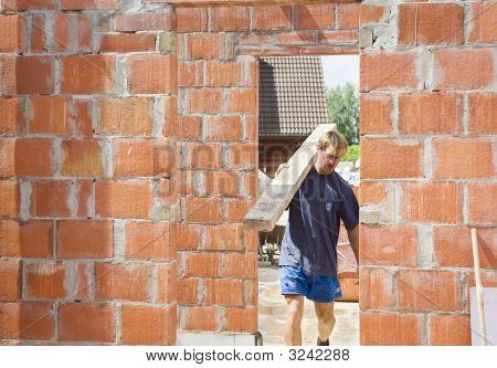 Builder Carrying A Wooden Beam