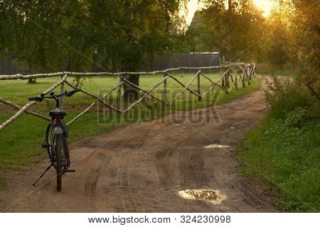 A Black Bicycle Is Leaning Against A Stand On The Side Of A Rural Road On An Early Summer Morning.