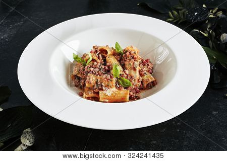 Exquisite Serving White Restaurant Plate of Homemade Rigatoni with Bolognese Sauce and Smoked Pork Belly. Stylish High Kitchen Italian Penne Pasta Tubes on Natural Black Marble Background