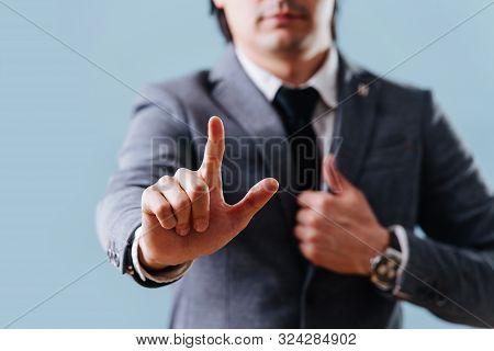 Businessman In Suit Making Objection Gesture , Holding Index Finger Up Over Blue