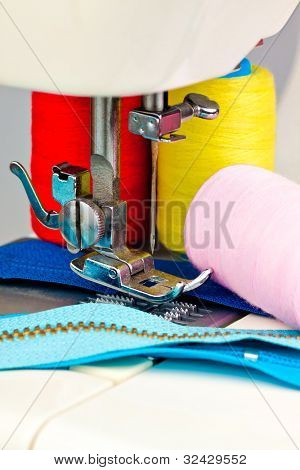 Macro image of a sewing machine , reels with thread and clothing accessories
