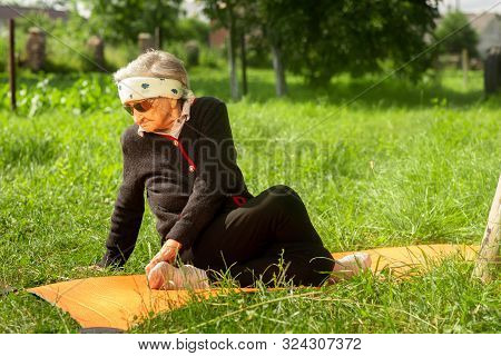 An Elderly Woman Of 90 Years Old, With Gray Hair And A Headband, Doing Fitness In The Garden On A Yo