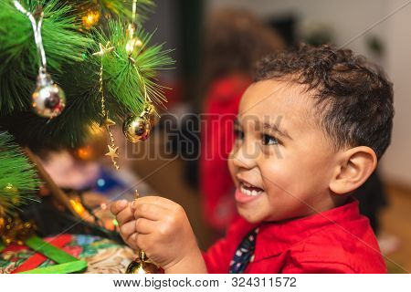 Little Boy Decorating Christmas Tree And Having Fun.