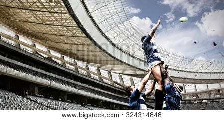 Strong Rugby Players against rugby stadium in the morning