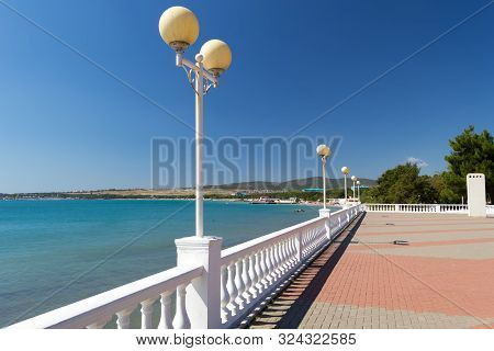 Beautiful Sea Promenade With White Decorative Fence With Balusters And Round Lanterns In Sunny Autum