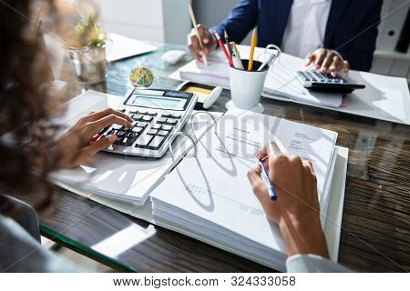 Two Business Colleagues Calculating Tax In Office